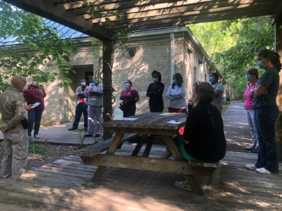 """Medical Director Dr. Charles Maresh (left) updates Free Health Clinic staff on """"keeping your work family healthy"""" during an outdoor meeting last week."""