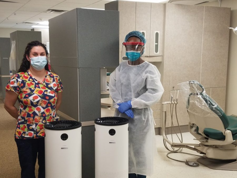 Dental Clinic Coordinator Sarah McClellan (left) and dental assistant Raven Davis are shown with the air filtration units in place in each of the dental operatories.