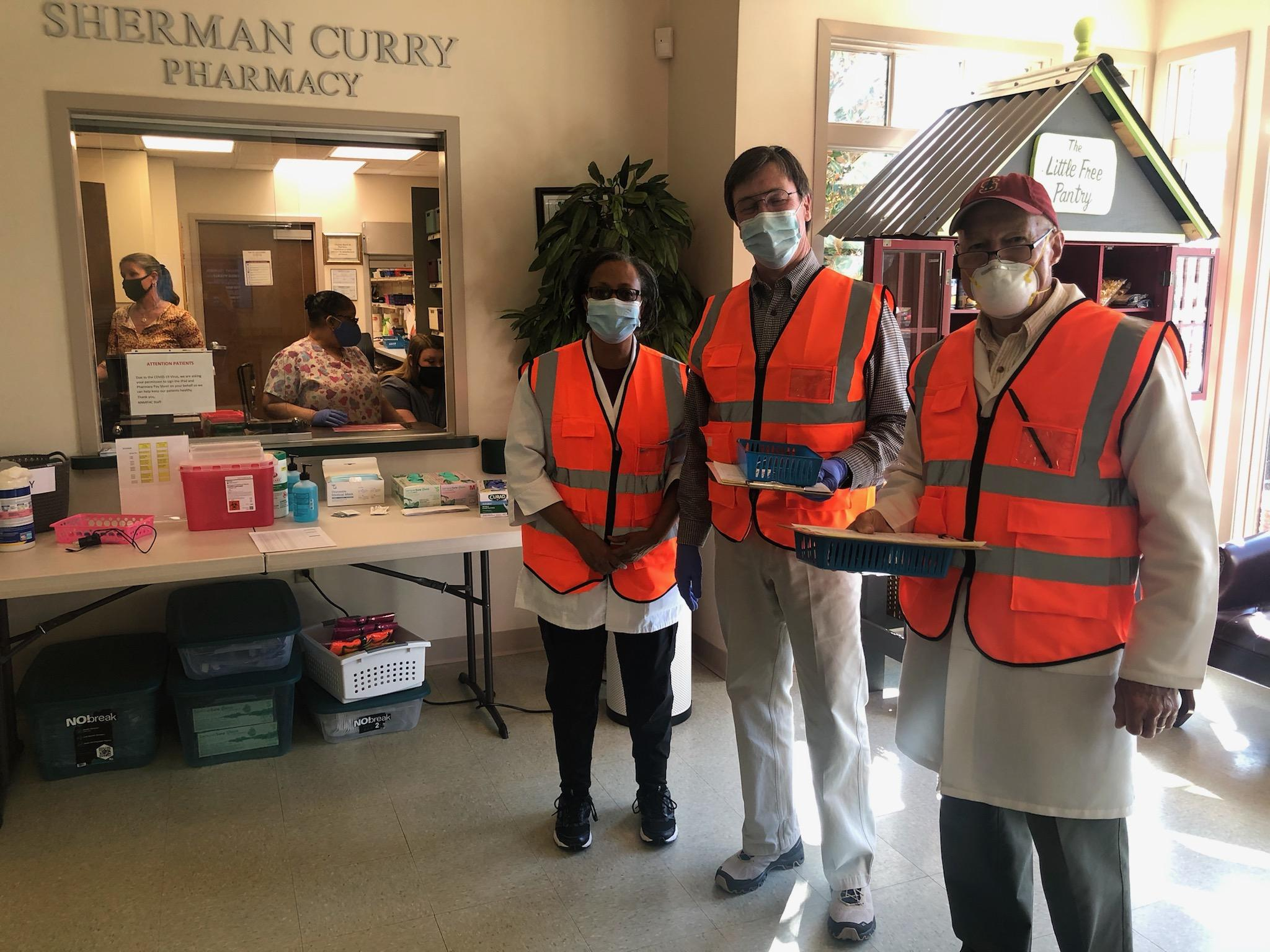 At left, behind the Pharmacy window, Pharmacist Britney Dedmond and Pharmacy Coordinator Angie Rich ready the syringes. In the lobby are three vaccinators – Pharmacist Beverly Thomas, Dr. Greg Lockhart, and Dr. Charles Maresh.